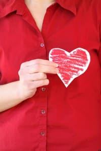 Woman holding paper heart cutout over chest